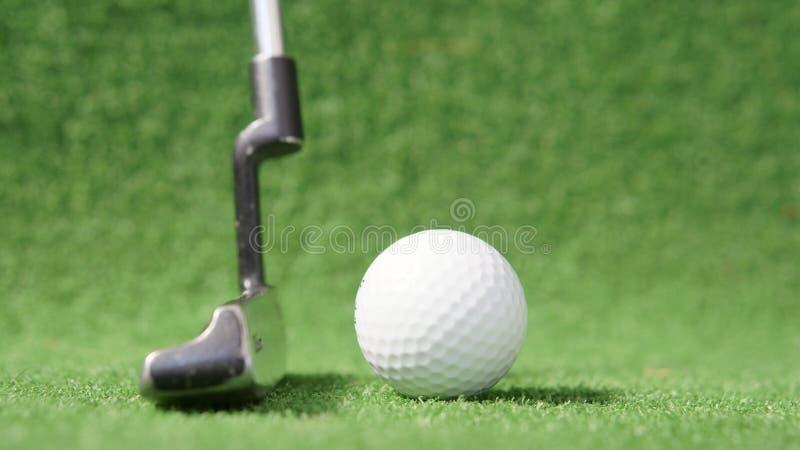 Golfboll och putter på gröngräs arkivbilder