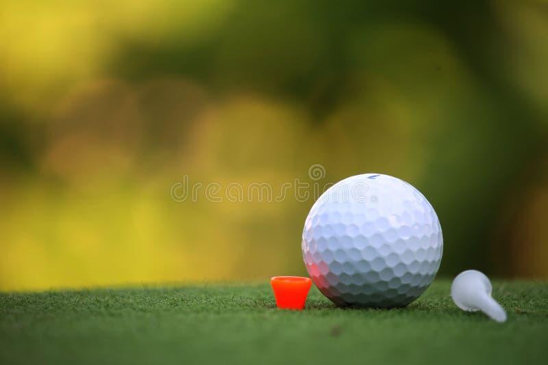 Golfboll och utslagsplats i aftongolfbanan med solsken i th arkivbilder