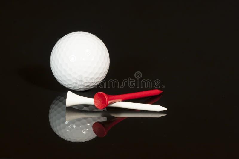 Golfboll och utslagsplatser arkivfoto