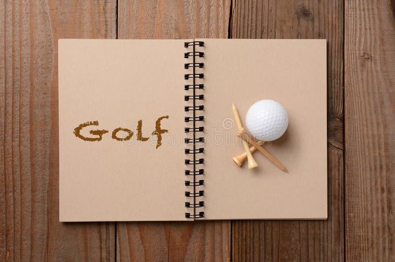 Golfboll och utslagsplatser på den öppna anteckningsboken fotografering för bildbyråer