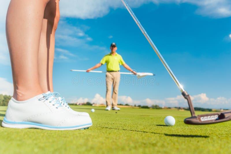 Golfboll på den sättande gräsplanen bak det låga avsnittet av en kvinnlig spelare royaltyfri bild