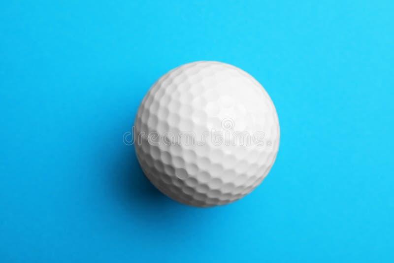 Golfboll på färgbakgrund Sportutrustning royaltyfria bilder