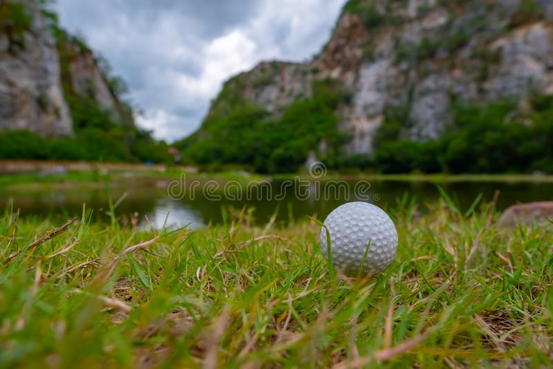 Golfboll på gräs nära den lilla sjön royaltyfri foto
