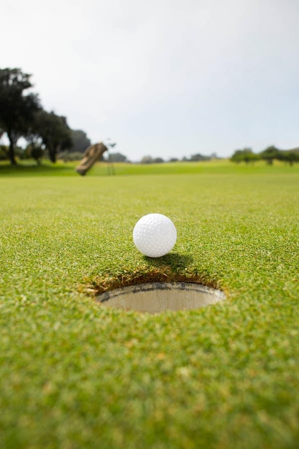 Golfboll på kanten av hålet royaltyfri bild