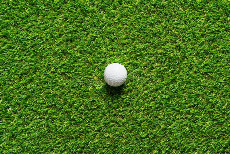 Golfboll på textur för grönt gräs av golfbanan för bakgrund arkivbild