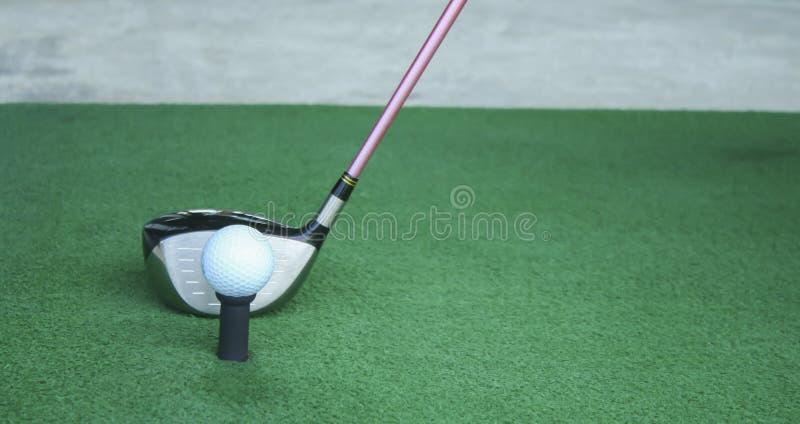 Golfboll på utslagsplats med chaufförklubban som är främst av chauffören som kör r royaltyfria bilder