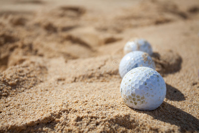 Golfbollar i en sand arkivbild
