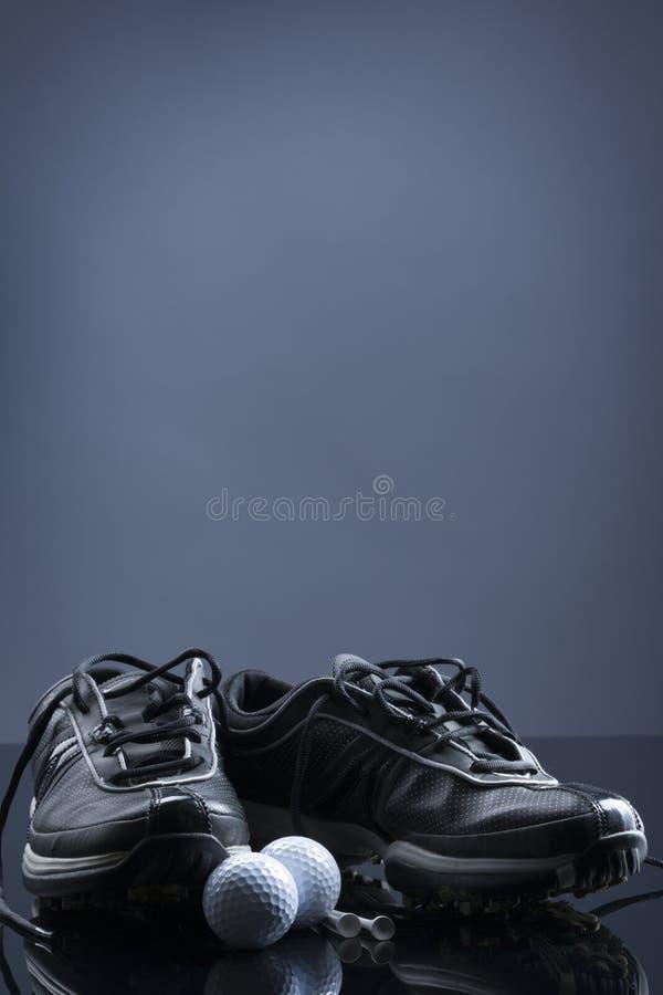 Golfbollar, utslagsplatser och skor på mörker - blå bakgrund royaltyfri bild