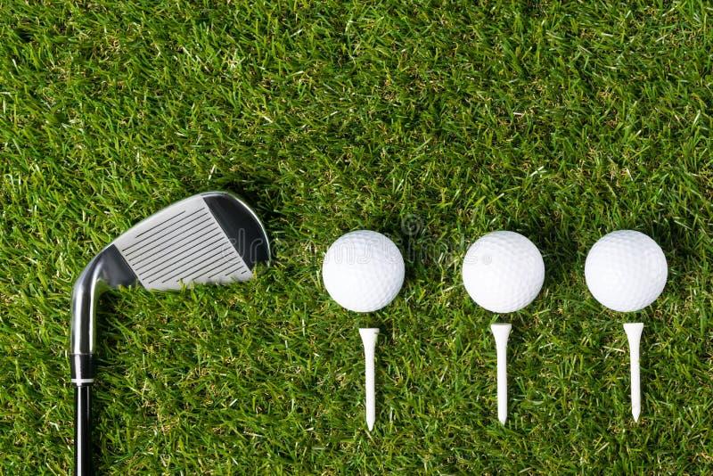 Golfclub und drei Bälle liegen schön auf dem grünen Gras lizenzfreies stockbild