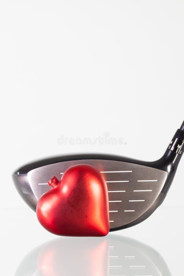 Golfclub und rotes Herz auf einem Glastisch lizenzfreies stockfoto
