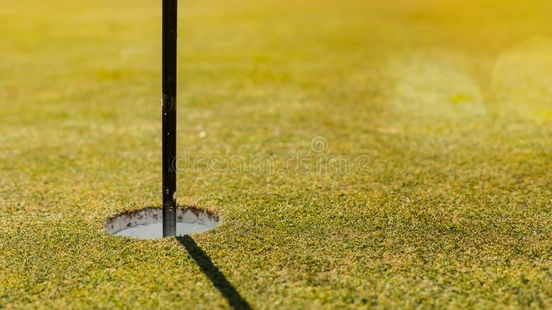 Golfcursus die groen gat met vlagpool zetten royalty-vrije stock foto