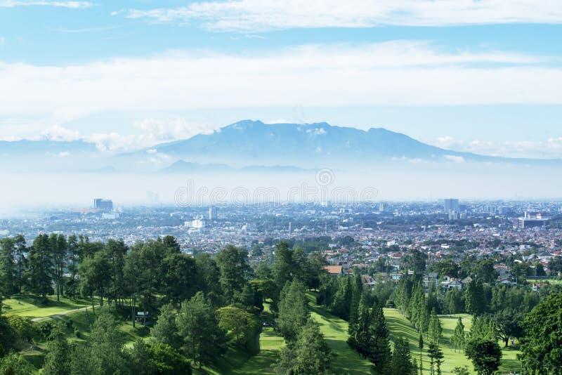 Golfcursus met nevelige Bandung-cityscape achtergrond stock foto