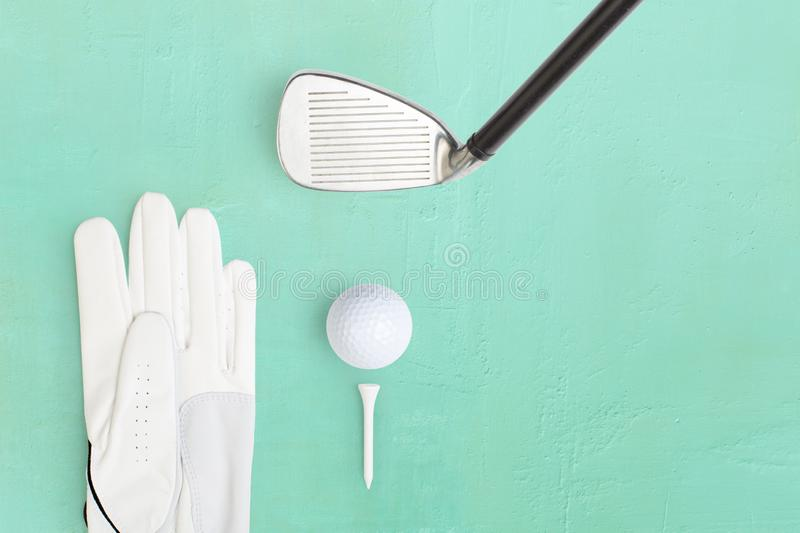 Golf ball and golf glove on a base in light green stock photos