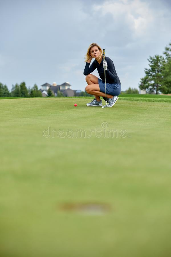 Golfer action to win after a long game of golf on a green field. The girl is playing golf. Golf concept, hole.  stock photography