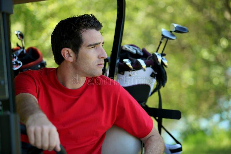 Golfer in buggy.