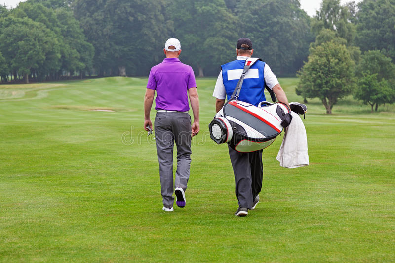 Golfer and caddy walking up a fairway. Golfer and caddy walking towards a ball on a par 4 fairway stock photos