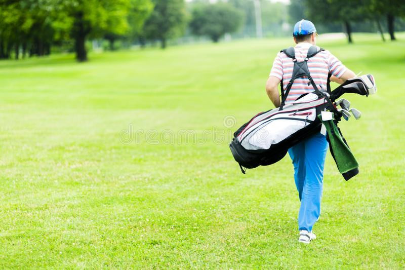 Golfer carrying his equipment royalty free stock photo