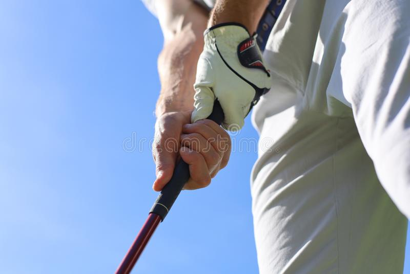 Golfer con un golf che tiene in mano un puter immagine stock libera da diritti
