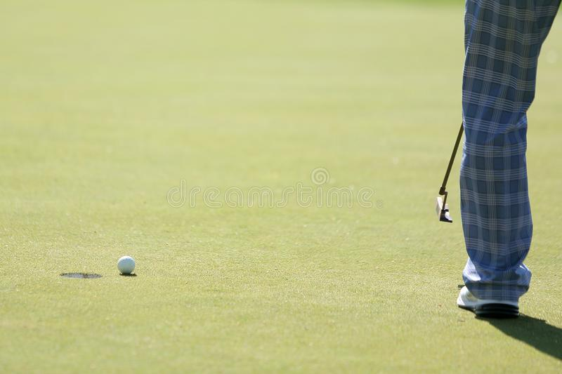 A golfer does the putting to a hole royalty free stock images