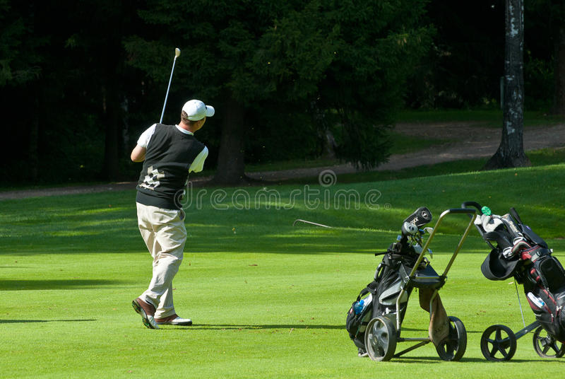Download Golfer finishes his swing editorial stock image. Image of club - 18738914