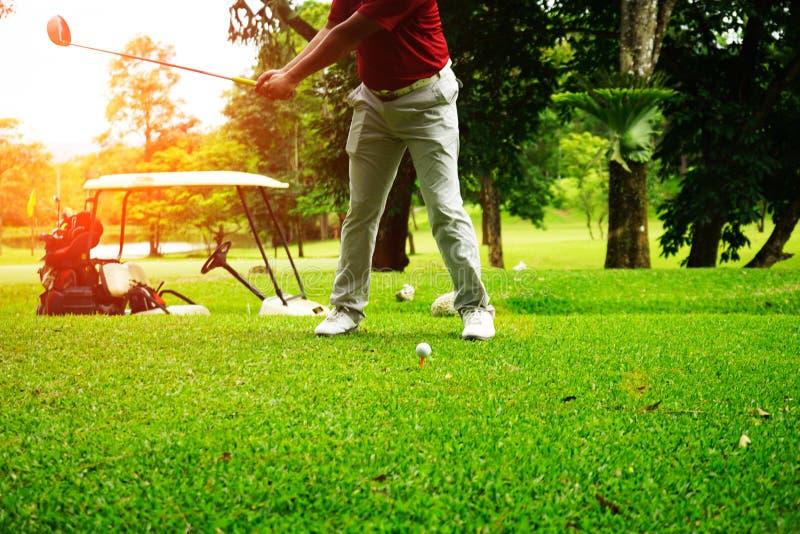 Golfer gioca a golf accanto alla golf car in un bellissimo campo da golf serale con il sole immagine stock