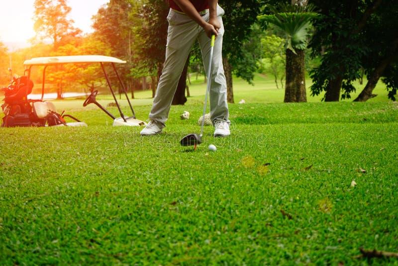 Golfer gioca a golf accanto alla golf car in un bellissimo campo da golf serale con il sole fotografie stock libere da diritti