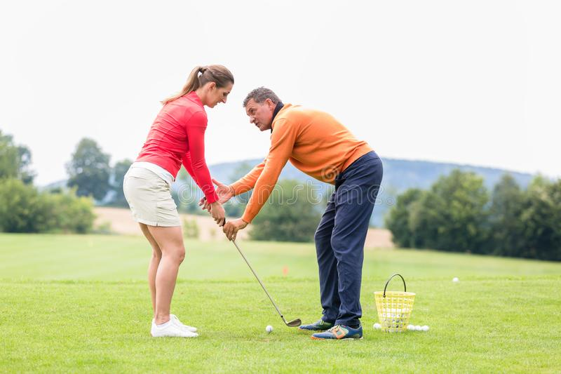 Golfer giving training to woman for taking a shot stock image