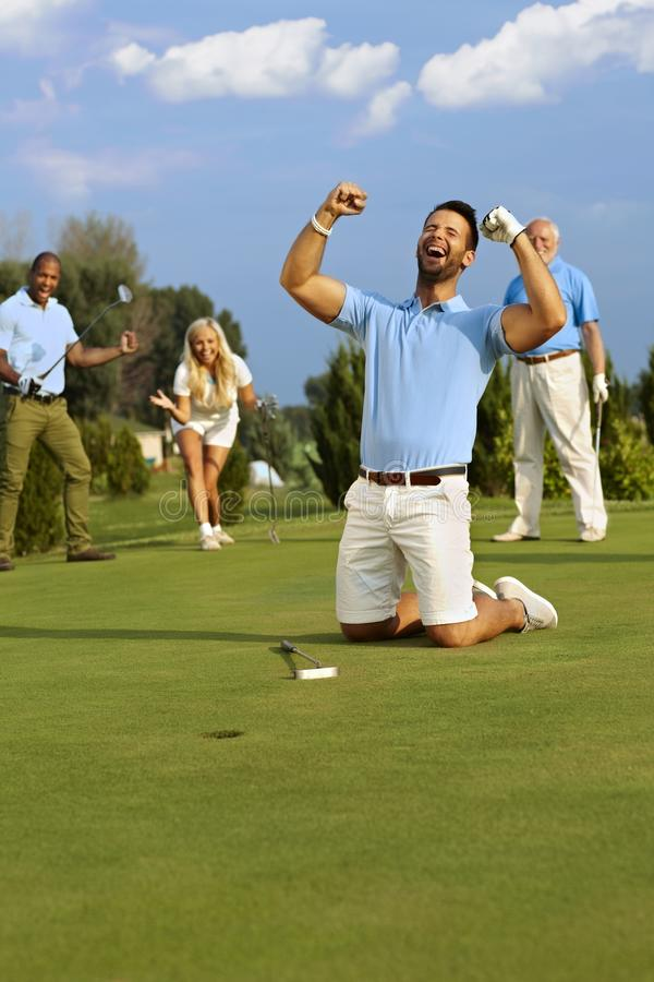 Golfer happy for putt. Young male golfer kneeling happy at hole after successful putt, shouting happy with hands fisted stock photos