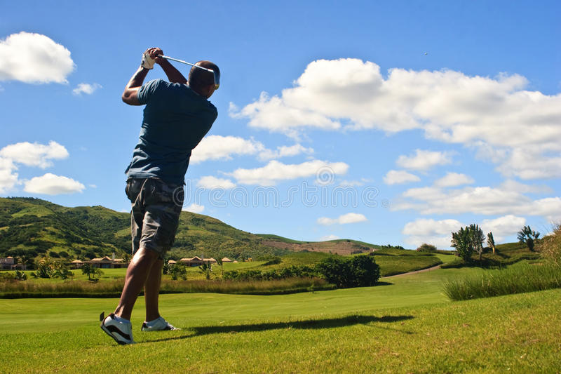 Golfer hitting the ball stock images