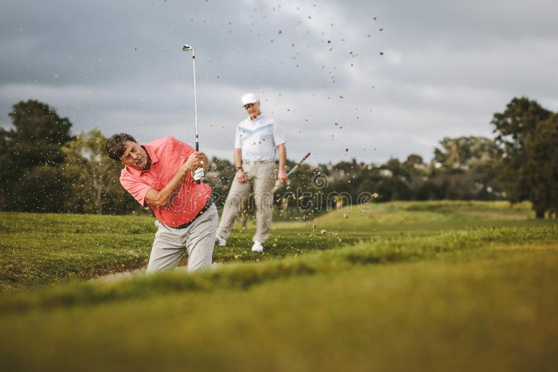 Golfer hitting the ball out of a sand bunker stock images