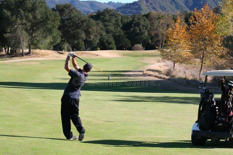 Golfer hitting down fairway stock image