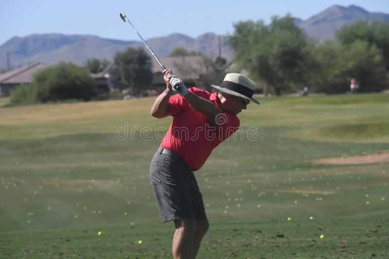 Male golfer hitting a golf ball from a back view. royalty free stock photography