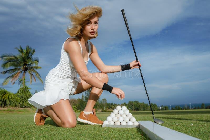Golfer. Lady golfer taking her white ball from ball set stock image
