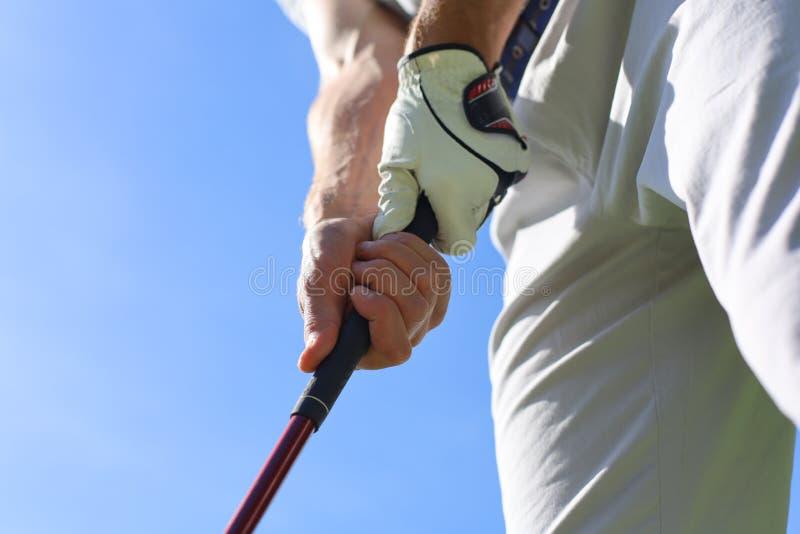 Golfer med golf som håller i en putter royaltyfri bild