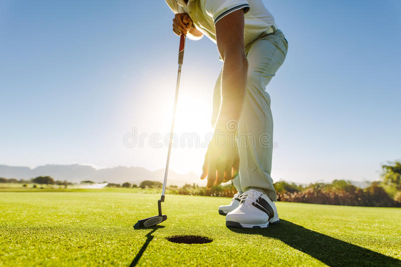 Golfer picking the ball from hole after put stock images