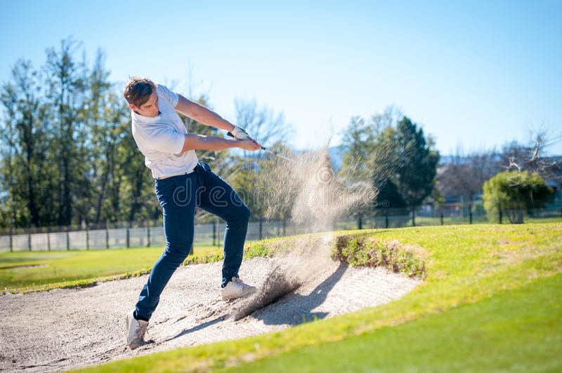 Golfer playing a chip shot onto the green stock images
