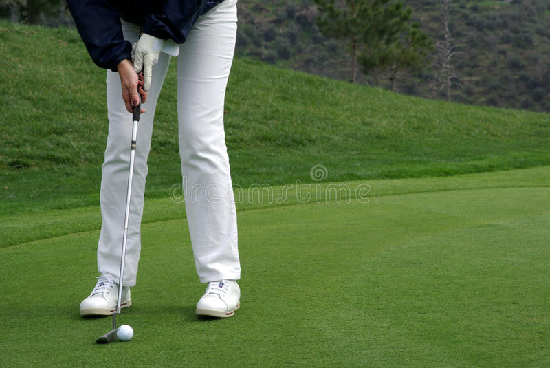 Golfer putting the ball stock photography