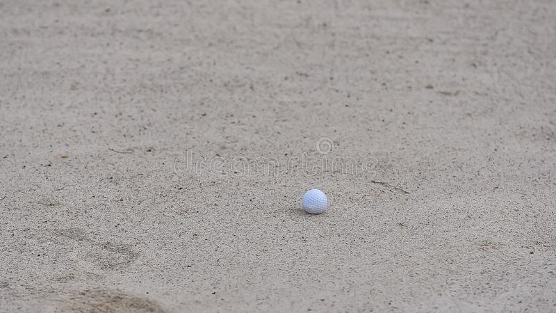 Golf ball putting on sand near hole golf to win in game at golf course with blur background and sunlight ray royalty free stock image