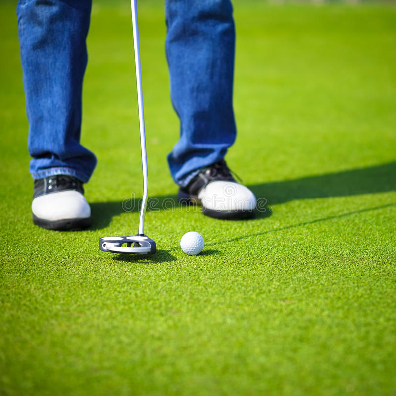 Golfer putting. Selective focus on golf ball stock photography