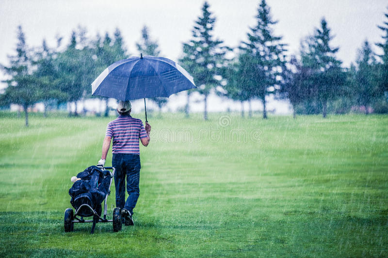 Golfer on a Rainy Day Leaving the Golf Course stock photography