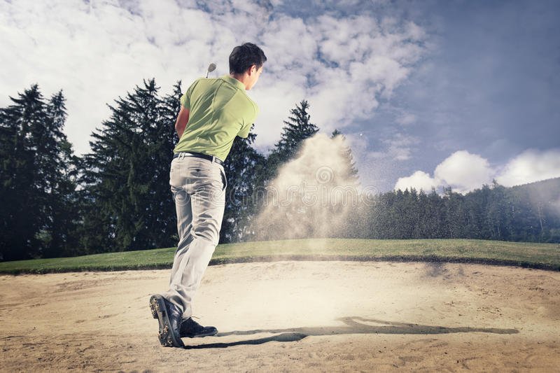 Golfer in sand trap. Male golf player in green shirt and grey pants hitting golf ball out of a sand trap with sand wedge and sand caught in motion stock image