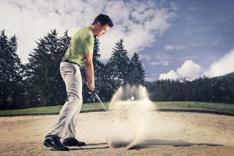 Golfer in sand trap. Male golf player in green shirt and grey pants hitting golf ball out of a sand trap with sand wedge and sand caught in motion stock photography