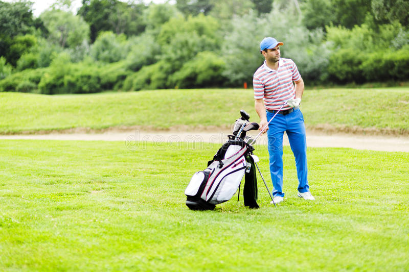 Golfer selecting appropriate club. For the next shot stock photo