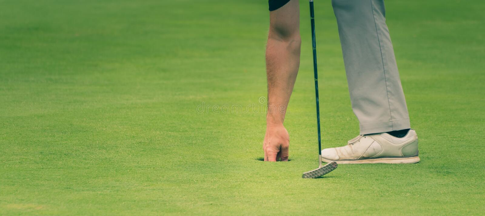 Golfer is taking the ball out of the hole royalty free stock photography