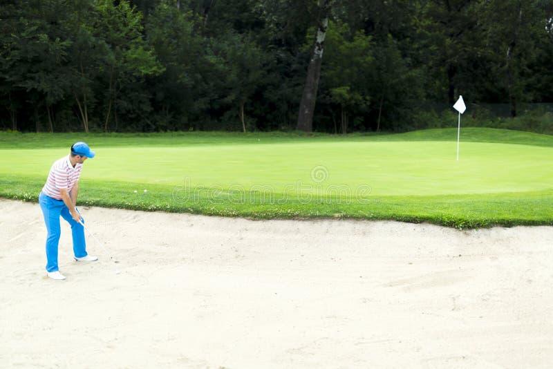Golfer taking a bunker shot stock photos
