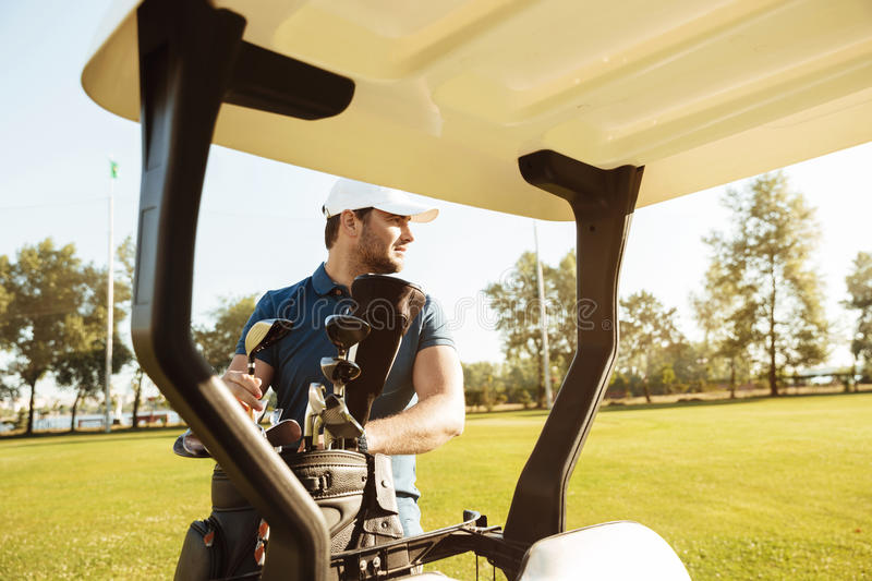 Golfer taking clubs from a bag in a golf cart. Concentrated male golfer taking clubs from a bag in a golf cart at the green course stock photography