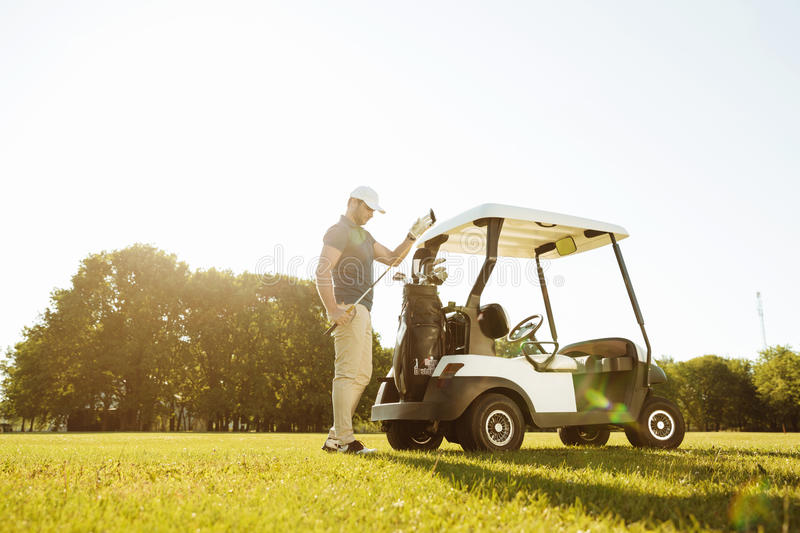 Golfer taking clubs from a bag in a golf cart. Young male golfer taking clubs from a bag in a golf cart at the green course stock photo