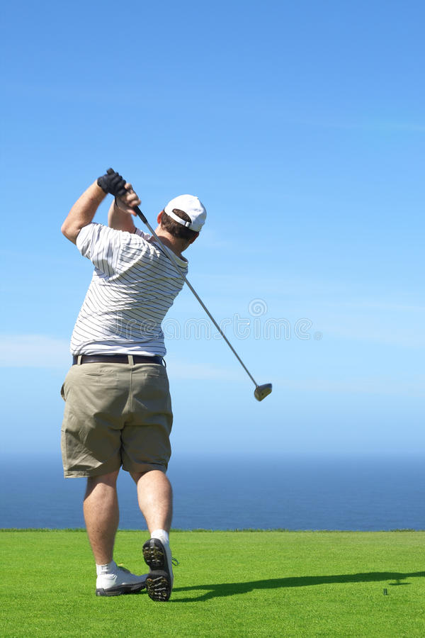 Golfer on the tee box. Young male golfer hitting the ball from the tee box next to the ocean on a beautiful summer day stock photo