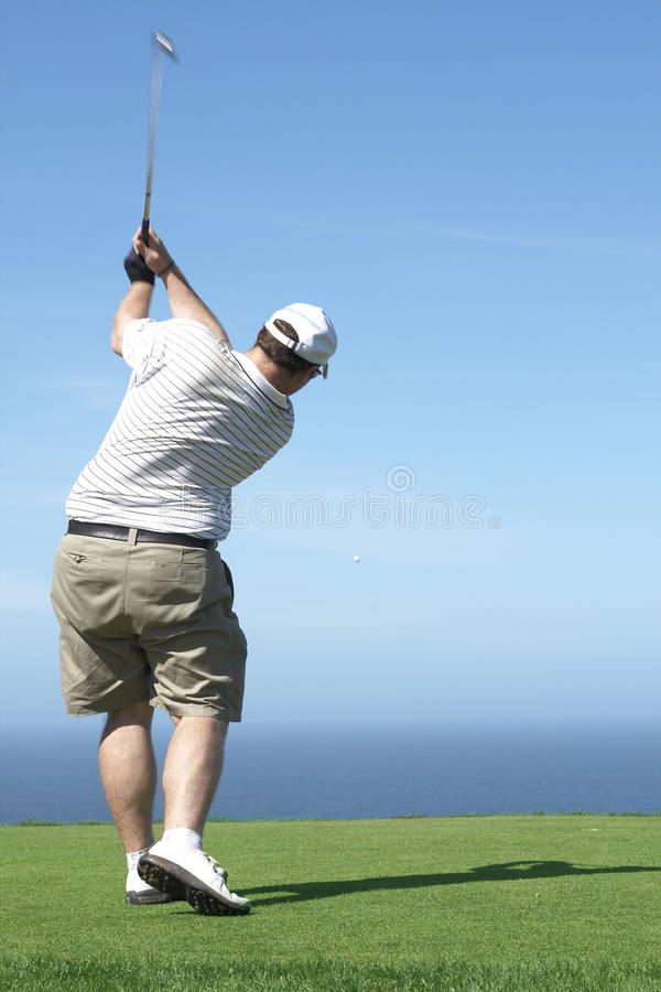 Golfer on the tee box. Young male golfer hitting the ball from the tee box next to the ocean on a beautiful summer day stock image