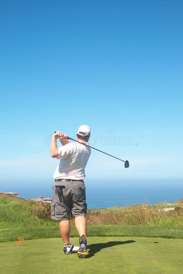 Golfer on the tee box. Young male golfer hitting the ball from the tee box next to the ocean on a beautiful summer day royalty free stock photos